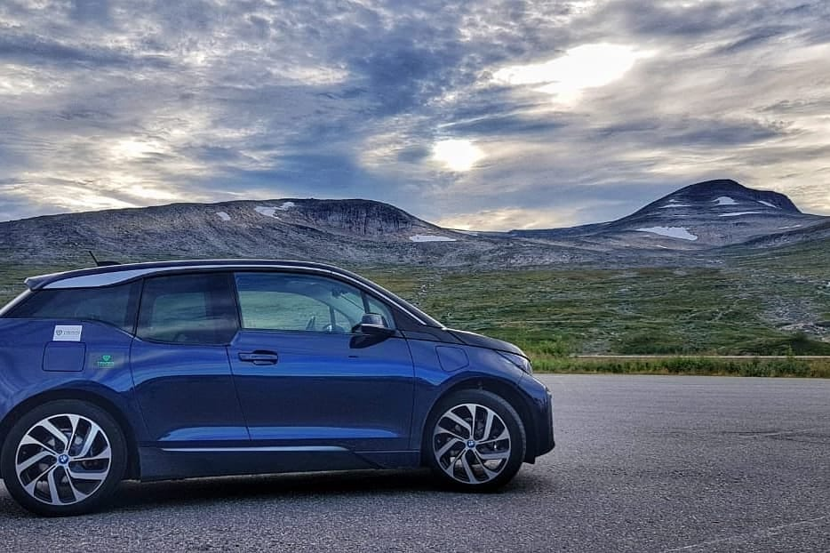 Blue BMW i3 against stunning mountain backdrop in Norway